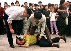 Politistii in civil persecuta in Piata Tiananmen un practicant Falun Gong care este trantit la pamant si amenintat cu un cutit la gat.