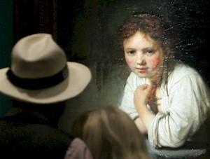 """Un cuplu priveste la pictura """"Tanara fata aplecata la fereastra"""" (1645), lucrare a faimosului pictor olandez Rembrandt, expusa in cadrul unei expozitii cu titlul """"Rembrandt. Cautarea unui geniu"""", la Galeriile Gemaelde, 03 August 2006 in Germania la Berlin."""
