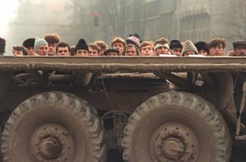 Bucuresti: Sub adapostul unui camion, bucurestenii privesc la luptele dintre Securitate si Armata pe 24 decembrie 1989.