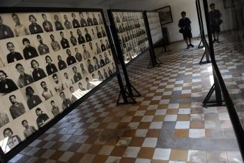 Un turist priveste fotografiile prizonierilor inchisi in S21 de regimul comunist condus de Pol Pot, care in numai 4 ani a eradicat o treime din popuatia Cambodgiei.
