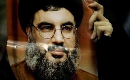 Un suporter al organizatiei teroriste Hezbollah, tinand o poza a liderului Hassan Nasrallah