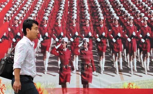 Un chinez langa un poster cu femei-soldat ale Armatei de Eliberare Populara - Armata Rosie chineza, 29 iulie 2010