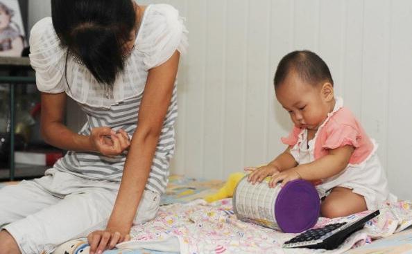 In varsta de 13 luni, fetita Xiaoying se joaca langa mama sa in Beijing, 9 august 2010, dupa ce a fost diagnosticata cu crestere prematura a sanilor