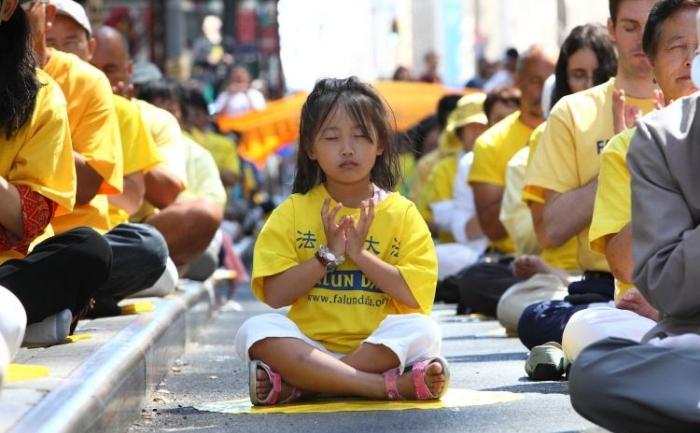 O copilă meditând lângă Piaţa Times Square, la o demonstraţie a exerciţiilor Falun Gong