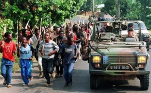 In aceasta fotografie, facuta in 27 iunie 1994, soldatii francezi trec pe langa luptatorii etnici hutu ai fortelor guvernamentale din Rwanda, in apropiere de Gisenyie, aproximativ 10 km de granita cu Zairul. Soldatii si militiile hutu au ucis aproape un milion de etnici tutsi.