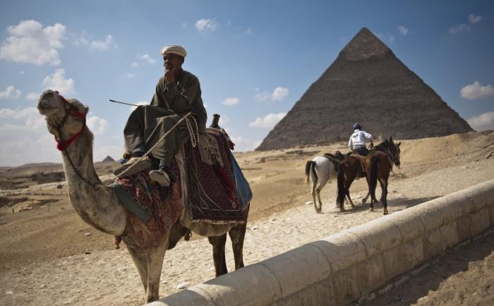 Egipteni, camile şi piramidele de la Gizeh, Egipt.
