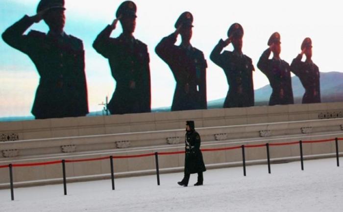 Un politist chinez în faţa unui ecran cu LED-uri din Piaţa Tiananmen in Beijing, China.
