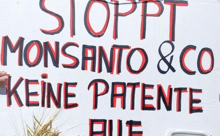 """Un barbat protesteaza si afiseaza o pancarta pe care este scris """"Fara patente asupra vietii, opriti Monsanto"""" in timpul unei demonstratii impotriva patentelor alimentare in Munich, Germania, 20 iulie 2010."""