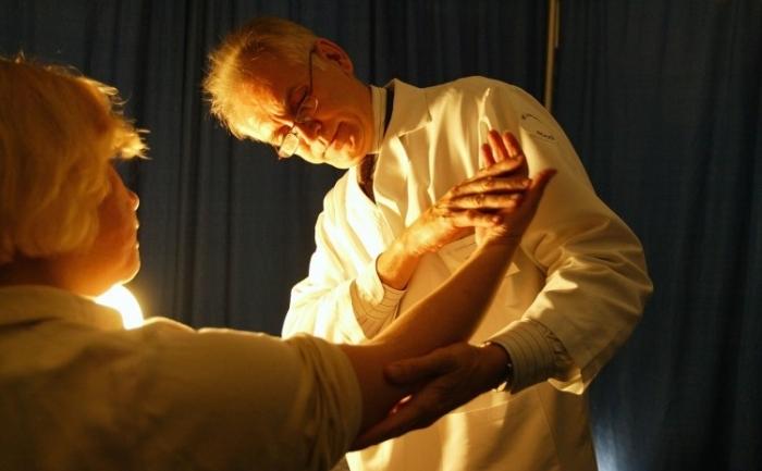 Un dermatolog cauta leziuni suspecte pe pielea unui pacient