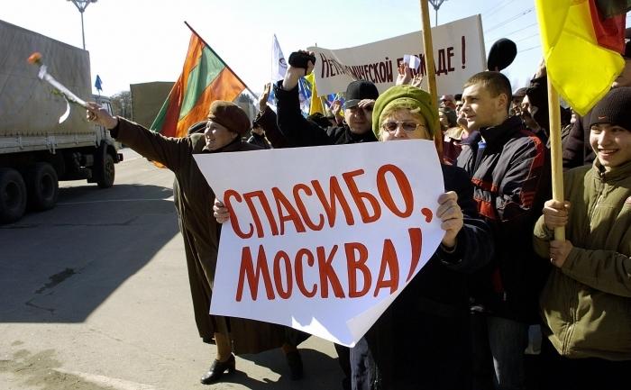 """Locuitori din Tiraspol primind cu urale ajutoare rusesti, in regiunea Transnistria - arhiva. Pe plancarda se poate citi """"Multumim Moscova!"""""""