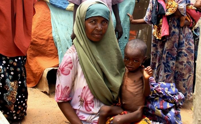 Kadijo Suleyman, refugiată internă din sudul Somaliei, îşi ţine copilul subnutrit în faţa adăpostului ei improvizat din tabăra Taraboonka.