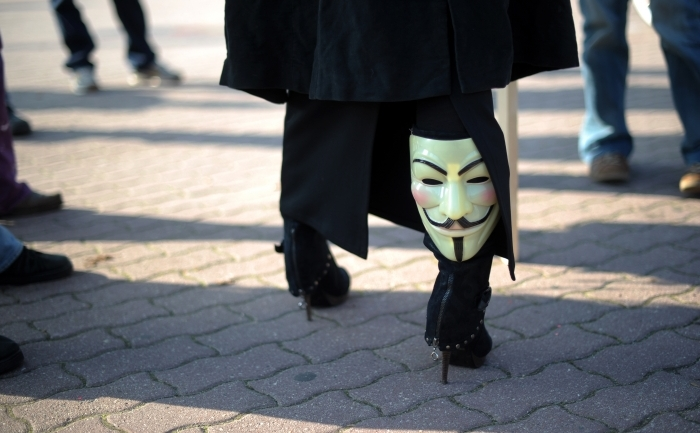 Masca grupului Anonymous Operations purtata de un sustinator.