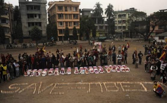 """Tibetanii se roagă lângă machete de sicrie în faţa cărora au pus lumănâri cu care stă scris """"Salvaţi Tibetul"""" în timpul unui miting în Siliguri pe 8 februarie, pentru a comemora sacrificiul călugărilor"""