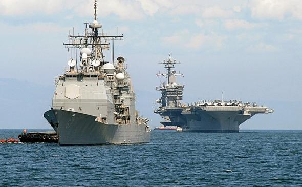 Portavionul american Carl Vinson (D) şi crucişătorul USS Bunker Hill (S) ancorate în Golful Manilla, 15 mai 2011. Grupul de nave americane protejează zona Pacificului, echilibrând puterea unei Chine din ce în ce mai agresive.