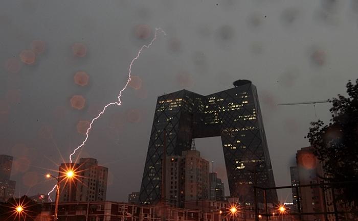 Un fulger lovind o zonă din Beijing, iulie 2011. Pe fundal se văd birourile televiziunii centrale de stat, CCTV