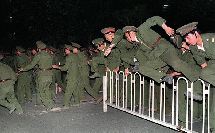 Soldaţii Armatei de Eliberare a Poporului sărind peste o barieră în Piaţa Tiananmen din centrul Beijingului, 4 iunie 1989, ȋn timpul mişcării studenţeşti pro-democraţie.