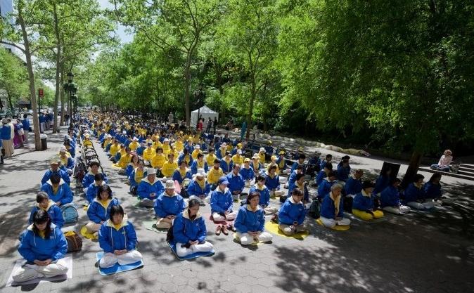 Sute de practicanţi Falun Dafa meditează în faţa clădirii ONU din New York, 13 mai 2012