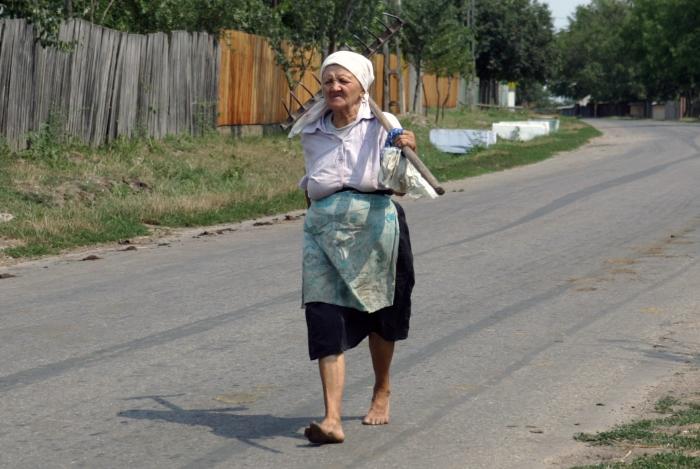Ţărancă din Moldova cu grebla pe umăr