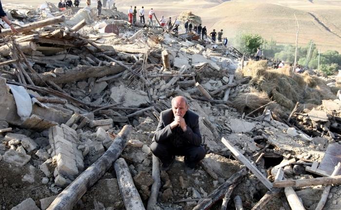 Un bărbat iranian stă în mijlocul molozului rămas în urma prăbuşirii casei sale după un cutremur în Iran.