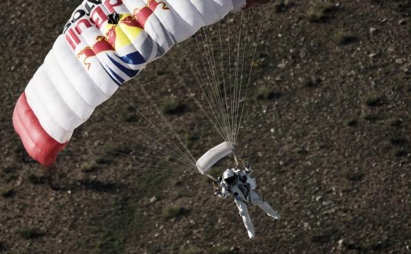 Austriacul Felix Baumgartner aterizează cu paraşuta în deşert, în timpul unui salt de pregătire, 25 iulie 2012, Roswell, New Mexico.