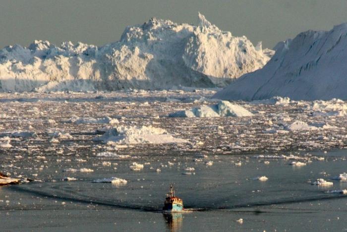 O barcă trece prin gheaţa ce se topeşte a fiordului Ilulissat pe coasta de vest a Groenlandei. Ţările riverane Arcticii îşi dispută supremaţia în zonă.