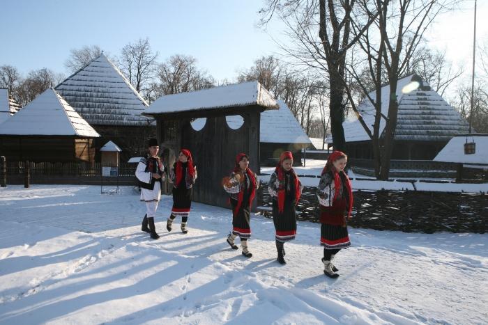 Copii în costule naţionale iarna, pe uliţa satului