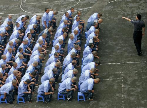 Deţinuţii ascultă un ofiţer de poliţie în timpul unei sesiuni de instruire comportamentale la închisoarea din Chongqing, 30 mai 2005.