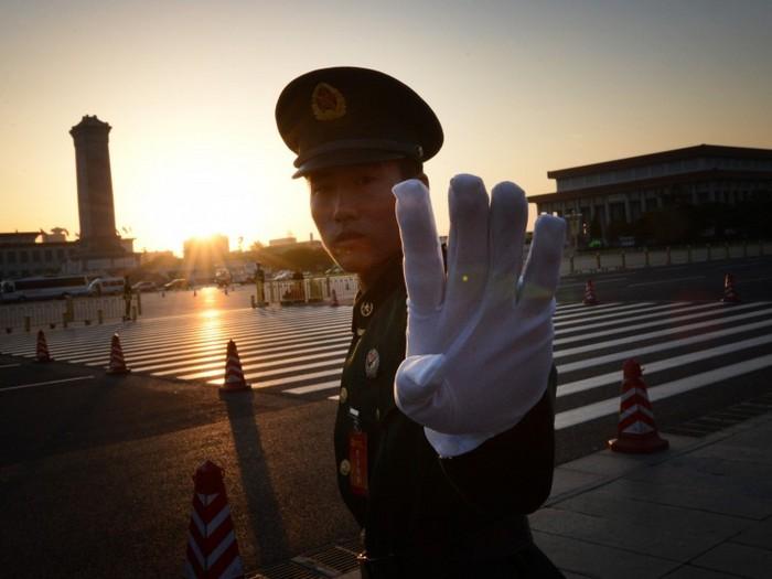 Un poliţist chinez reactionează la un aparat de fotografiat în afara Beijing-ului la 8 noiembrie 2012
