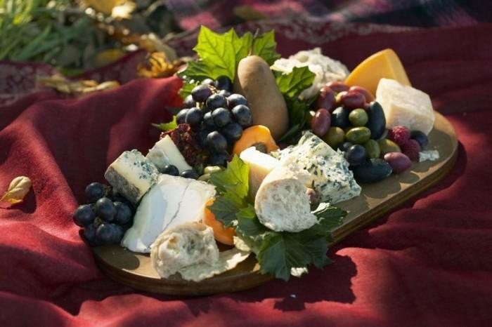 Un aperitiv frumos aranjat de brânză cu măsline şi struguri, servit pe un platou de lemn