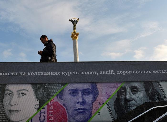 Un om stă lângă o pancardă care arată lire sterline, dolari americani şi bancnote ucrainene într-o zi caldă în Kiev, Ucraina, 12 noiembrie 2012.