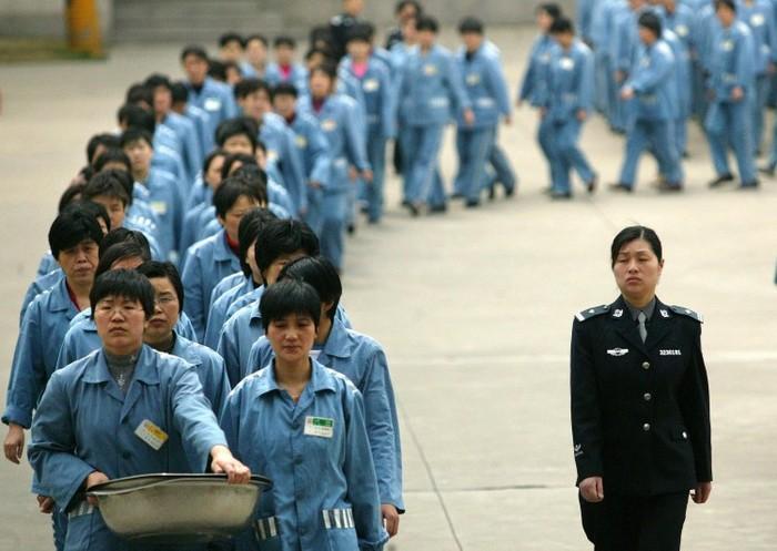 Deţinuţi care meg alături de o escorta de poliţie în timpul unei zile a porţilor deschise la o închisoare din Nanjing, în estul Chinei, la 11 aprilie 2005.