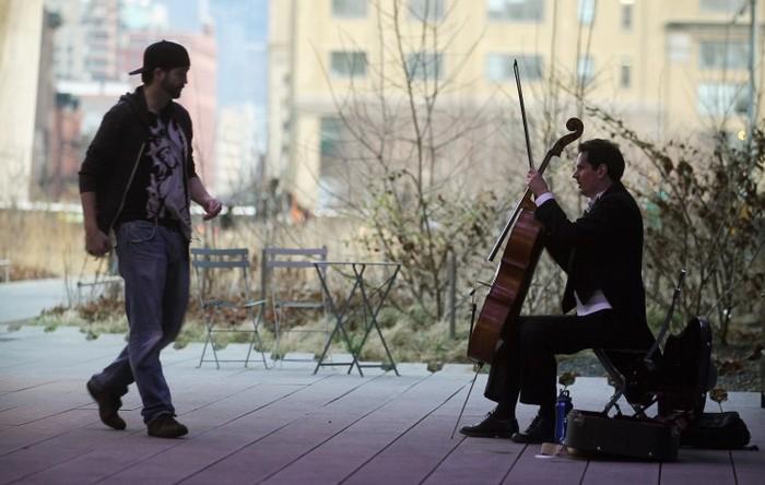 Un trecător dă bani unui muzician în parcul High Line din New York.