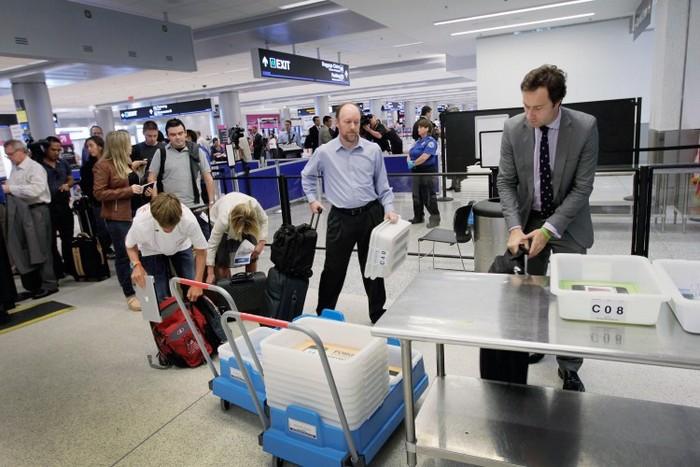 Pasagerii aşteaptă să treacă de controalele de securitate.