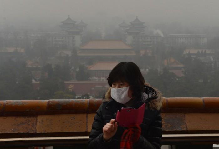 Un turist chinez face fotografii din parcul istoric Jingshan, în timp ce smogul continuă să învăluie Beijing-ul, la 31 ianuarie. Un raport recent susţine că Beijing-ul suferă de suprapopulare.