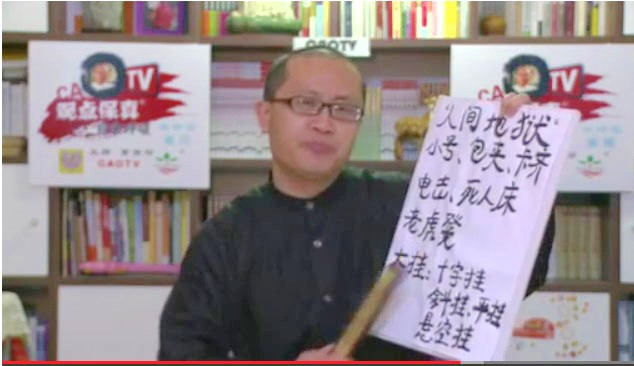 Cao Baoyin a ţinut o pancardă cu numele metodelor de tortură folosite în lagărul de muncă Masanjia. Trebuia sa facă un show web despre un forum economic, dar în schimb a spus ce avea pe inimă despre rapoartele de tortură extremă.