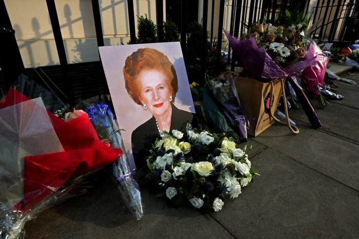 Un portret al fostului prim-ministru Margaret Thatcher este lăsat lângă florile din faţa reşedinţei ei din Piaţa Chester din Londra, la 8 aprilie 2013.
