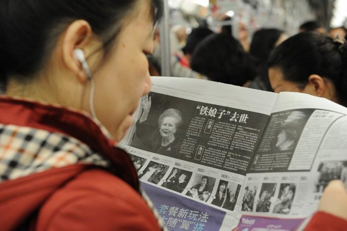 O femeie din China citeşte despre moartea fostului prim-ministru britanic Margaret Thatcher din ziua precedentă, la 9 aprilie 2013. Partidul comunist a interzis acum utilizarea de rapoarte străine de către mass-media de pe continent.