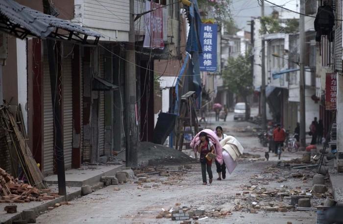 Oamenii îşi transportă bunurile în timp ce trec prin satul Gucheng lovit de cutremur, provincia sud-vestică chineză Sichuan, 20 aprilie 2013.