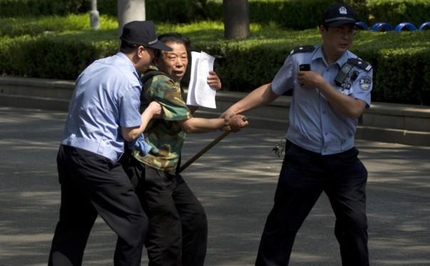Fotografie realizată în 8 mai 2012: un petiţionar care încearcă să atragă atenţia publicului este ridicat de poliţişti în faţa unui spital din Beijing în care era reţinut activistul orb Chen Guangcheng.