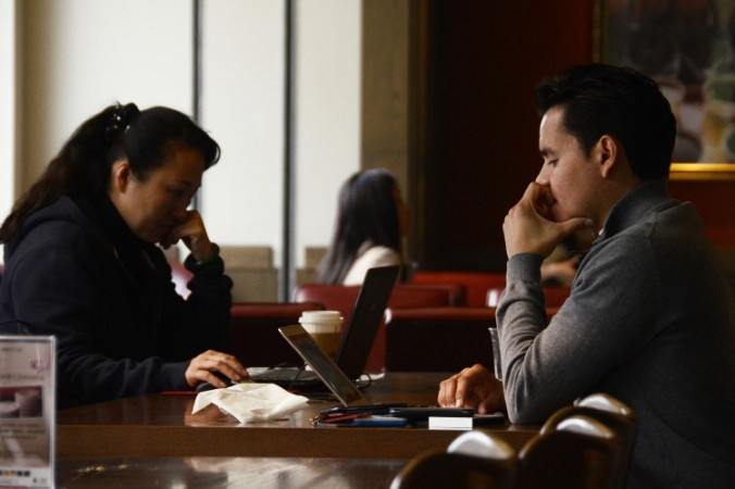 Oamenii îşi folosesc laptop-urile la o cafenea din Beijing în noiembrie, 2012