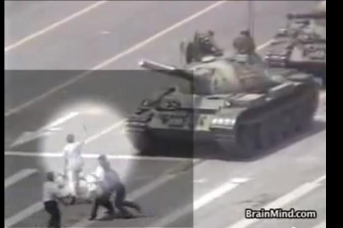 Captură video a scenei care a înconjurat Planeta, un manifestant singur în faţa tancurilor armatei chineze, în timp de poliţişti îl împingeau de pe carosabil