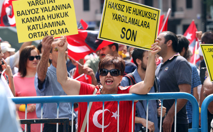 """O femeieţine o pancardăpe care stăscris: """"Puneţi capăt unui proces fărălege"""", 15 iulie 2013,în Ankara."""