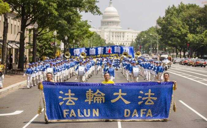 Trei practicanţi Falun Dafa conduc Fanfara  Divin Land cu un banner albastru şi auriu, Washington, DC, 18 iulie, 2013
