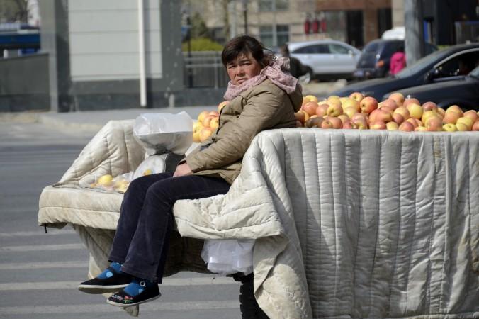 Vânzătoare ambulantă din Beijing stând pe o remorcă plină cu mere, 14 aprilie 2013. Astfel de comercianţi sunt adesea hărţuiţi sau loviţi de Chengguani, bătăuşi angajaţi de autorităţile locale.