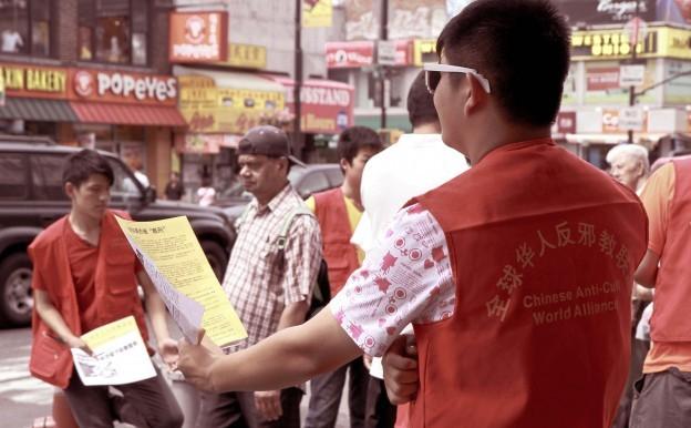 Un grup de tineri de 16 ani, încearcă să dea materialele ale PCC, care incită la ură,  trecătorilor de pe Main Street in Flushing, New York, la 10 august 2013