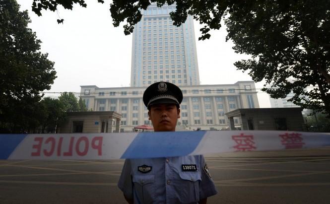 Poliţia sta de pază în a treia zi a procesului politicianului căzut în dizgraţie Bo Xilai la Tribunalul Popular Intermediar în Jinan, provincia Shandong, la 24 august 2013. În procesul lui Bo Xilai, secretele familiei sale au fost expuse, dar Partidul Comunist din China a fost cruţat