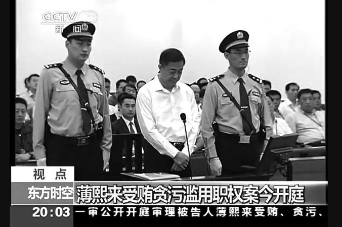 Fost membru al Biroului Politic Bo Xilai se află între două gărzi la Curtea intermediară Jinan, provincia Shandong pentru prima zi a procesului său pe 22 august. Procesul lui Bo a fost negociat să fie depolitizat, potrivit experţilor.