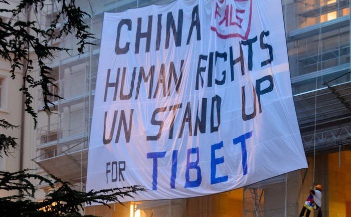 Activişti tibetani desfăşuară un baner uriaş în timpul unei demonstraţii pe 22 octombrie 2013, pe o cladire a Naţiunilor Unite de la Geneva.