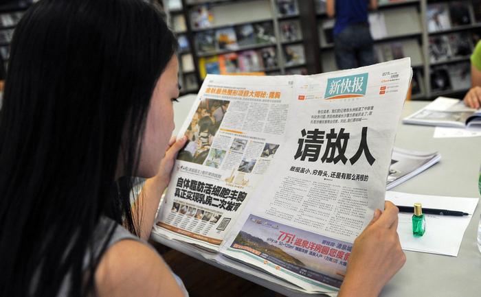 """O femeie citeşte ziarul Noul Expres, care pe 23 oct 2013 a publicat un editorial de o pagină, cu titlul """"Vă rugăm eliberaţi-ne omul""""."""