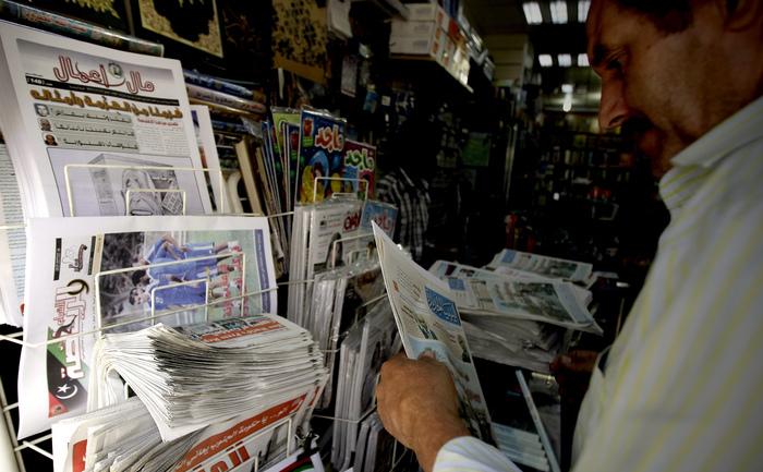 Un libian îşi cumpără ziarul de la un chioşc de ziare din Tripoli.